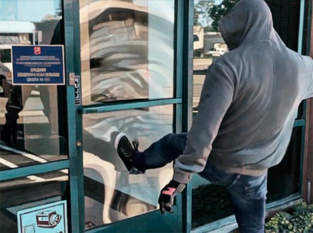 Нарушитель атакует входную дверь школы.