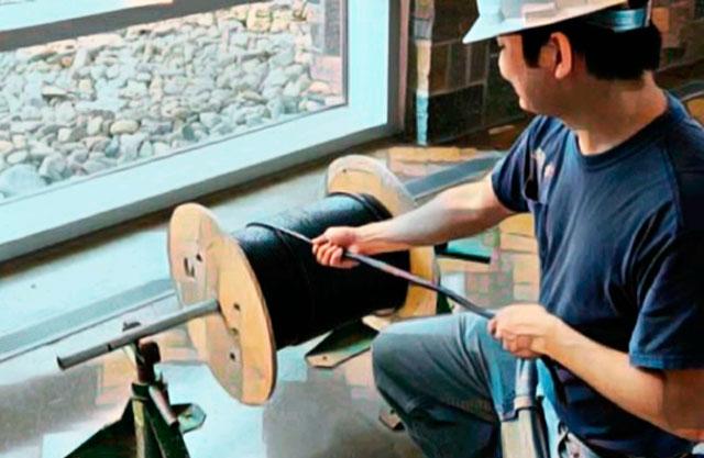 Монтажник сматывает кабель видеонаблюдения с барабана